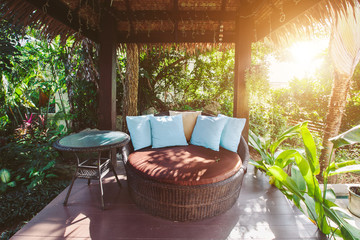 Cozy luxury gazebo chair with pillows in villa yard
