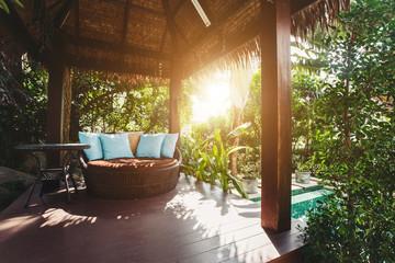 Cozy luxury gazebo chair with pillows in villa yard