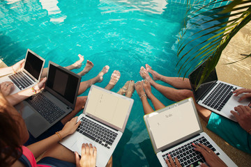 Group of people freelancers using laptop computer sitting near swimming pool and work together