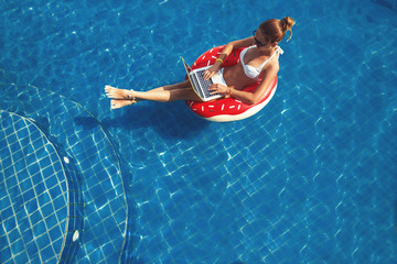 Pretty female in swimsuit and sunglasses sitting in swimming ring in pool, enjoy and using laptop. Shopping online, working outdoor concept