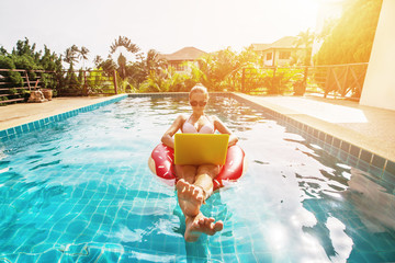 Pretty woman in swimsuit and sunglasses sitting in swimming ring in pool, enjoy and using laptop. Shopping online, freelance concept, summer travel