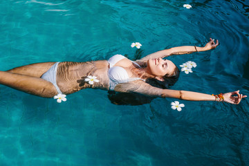 Beautiful female in swimming pool background with white Spa flowers