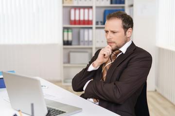 manager schaut mit ernstem gesicht auf sein notebook