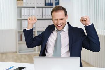 mann im büro freut sich und ballt beide fäuste