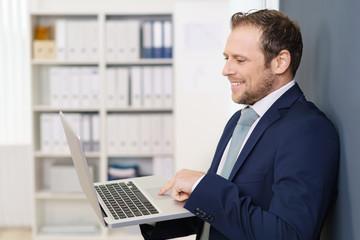 geschäftsmann steht im büro und schaut auf sein notebook