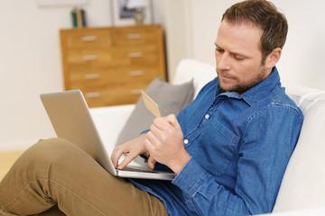 mann sitzt auf dem sofa mit laptop und kreditkarte