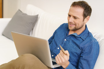 lächelnder mann mit notebook und kreditkarte zu hause