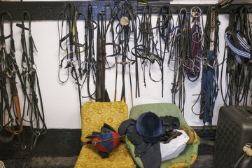 Riding tack on hooks and riding gear on an old armchair in a stable.