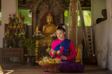 Beautiful Thai Women in Lanna traditional costume making offerings of incense candles to a Buddha at  Chiang mai, Thailand