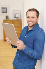mann steht in seiner wohnung und hält ein tablet in den händen