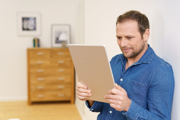 mann schaut zu hause auf sein tablet