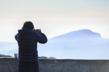 people takes photo of mountain by smart phone