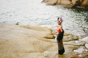Beautiful Thai girl in Thailand traditional dress with flowers on her hair style on sea shore