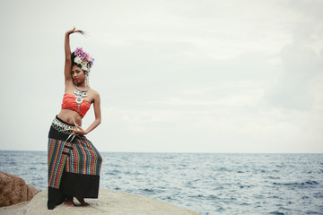 Portrait of dancing Thai girl in Thailand traditional dress with flowers on her hair style on sea shore