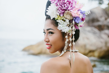 Portrait of smiling Thai girl in Thailand traditional dress with flowers on her hair style on sea shore