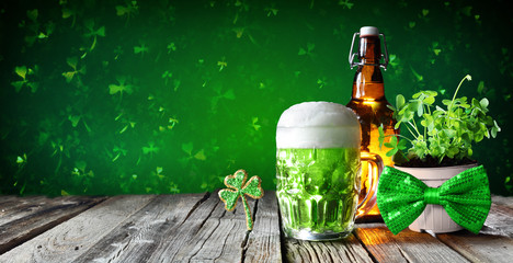 St Patrick's Day - Green Beer In Glass With Bottle And Clovers On Wooden Table