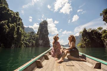 Yang girls traveling by boat exploring epic limestone cliffs in huge lake in Khao Sok National Park, Chiew lan lake, Thailand
