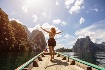 Happy female traveling by boat in mountain tropical lake, the wind fluttering hair. Summer Travel concept, Thailand, Cheow lan lake