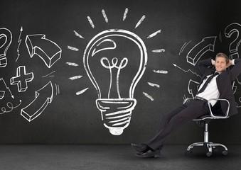 Businessman relaxing on chair against light bulb on blackboard