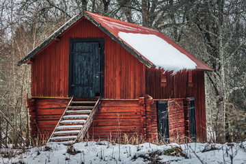 Old wooden barn in faded red color, standing in the forest in Sweden