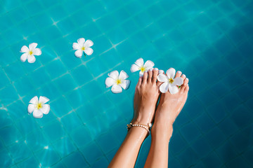 Beautiful female foot in swimming pool background with white Spa flowers
