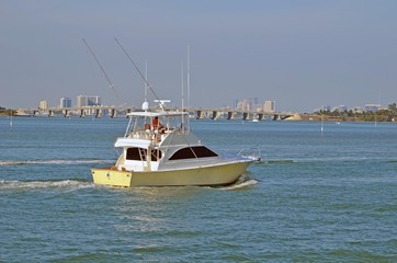 Sport Fishing Boat on the Florida Intra-coastal Waterway with the Julia Tuttle causeway bridge and Miami and North Miami beach skylines in the distant background.