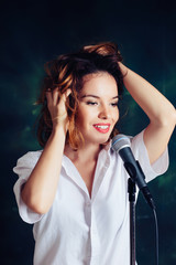 Studio Portrait of woman singing with microphone over dark green background
