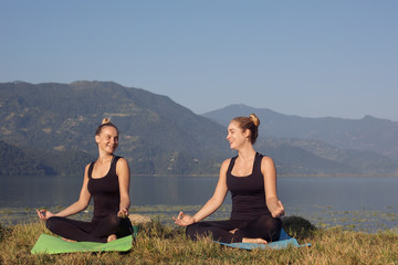 Young girls practicing morning yoga meditation outdoor on mountain lake