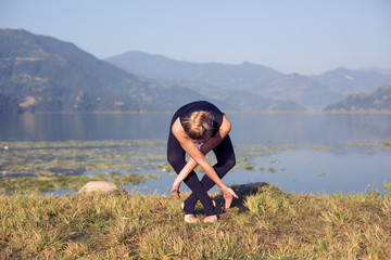 Young woman practicing morning yoga outdoor on mountain lake