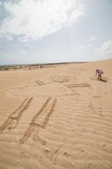 enfant dessinant sa famille sur le sable