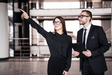 Young businesswoman showing something to businessman seen through glass in office