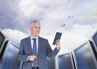 Businessman using digital tablet against server systems in sky