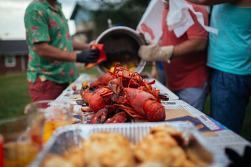 People preparing a large lobster boil outdoors