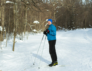 Man in a blue suit runs on skis in the winter woods.