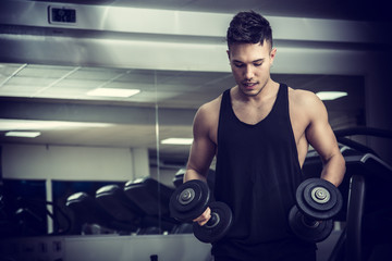 Handsome muscular young man exercising biceps in gym with dumbbells