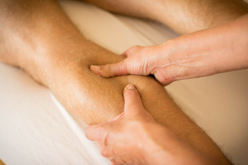 Therapist applying pressure on male leg - hand massage of human calf muscle