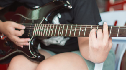 Women playing electric black guitar instrument