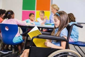 Disabled school girl on wheelchair reading a book in classroom