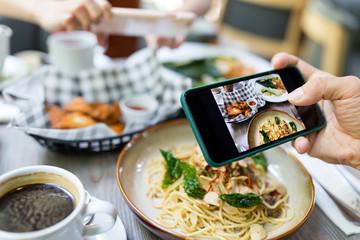 Friends taking photo on cellphone in restaurant