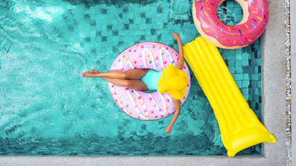 Woman relaxing on inflatable ring in pool