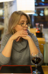 Blonde woman has dinner in japanese restuarant  with sushi and drink red wine
