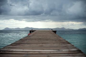 Wooden pier in the sea. Storm begins.