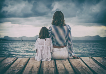 Woman and little girl sitting on the wooden pier near the sea.
