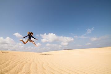 jeune femme bondissant dans les dunes
