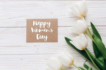 happy womens day text sign on stylish craft greeting card and tulips on white wooden rustic background. flat lay with flowers and gift blank paper with space for text.