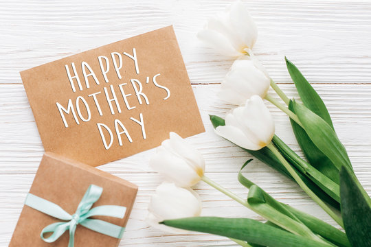 happy mothers day text sign on stylish craft present with greeting card and tulips on white wooden rustic background. flat lay with flowers and gift with space for text. greeting card