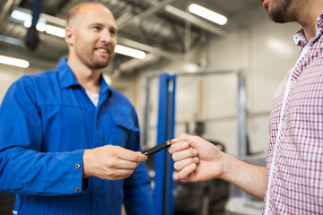 auto mechanic giving car key to man at workshop