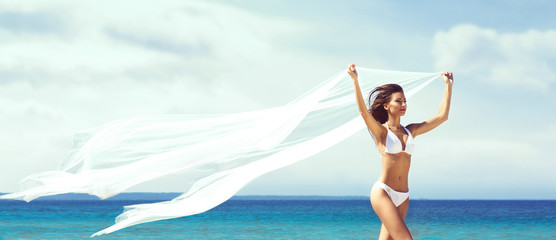 A beautiful woman in a swimsuit posing on a beach at summer. Holiday, vacation, resort, concept.