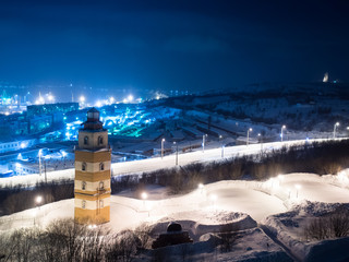 Night image of the city of Murmansk and the Memorial Complex of the sailors who died in peacetime with beacon tower against the backdrop of the sea port and snow covered streets and Alyosha monument