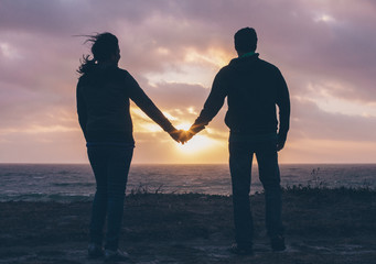 Couple holding hands by sea at sunset